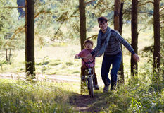 Father learning his son to ride on bicycle outside, real happy family in summer forest enjoing nature Stock Photography