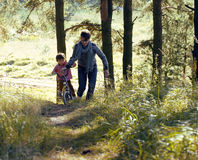 Father learning his son to ride on bicycle outside, real happy family in summer forest enjoing nature Royalty Free Stock Photo