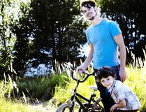 Father learning his son to ride on bicycle outside, real happy f Stock Photos