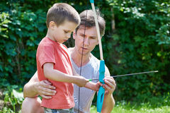 Father is learning his son to shoot from bow Royalty Free Stock Photos