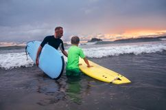 Father learning his son to surf at sunset time royalty free stock image