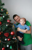 Father lift baby boy next to the Christmas tree Stock Photography