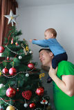 Father lift baby boy next to the Christmas tree Royalty Free Stock Photos