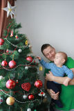 Father lift baby boy next to the Christmas tree Royalty Free Stock Image