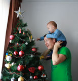 Father lift baby on his shoulders next to the Christmas tree Stock Photo