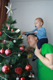 Father lift concentrated baby boy next to the Christmas tree Stock Image