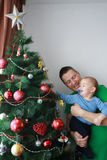 Father lift smiling baby boy next to the Christmas tree Royalty Free Stock Photos