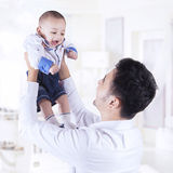 Father lift up male infant in the bedroom Royalty Free Stock Images