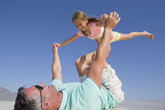 Father lifting daughter on sunny beach Stock Image