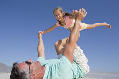 Father lifting daughter on sunny beach Stock Photography