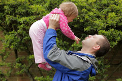 Father lifting daughter up Stock Photography