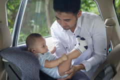 Father Lifting his Baby from The Car Seat Stock Image
