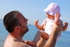 Father lifting his baby daughter on the beach Stock Photos