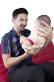 Father lifting his baby on sofa Royalty Free Stock Photos