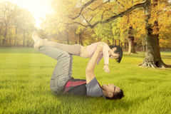 Father lifting his daughter at autumn park Royalty Free Stock Image