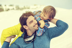 Father lifting his son affectionately in the snow with tenderness. In mountain Royalty Free Stock Photo