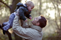 A father lifting his son in the air Royalty Free Stock Photos