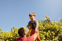 Father lifting his son high in the air Stock Photography