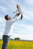 Father lifting his son up in the sky Royalty Free Stock Photos