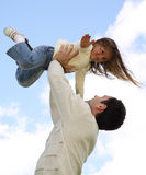 Father lifting little daughter. Young girl on father's arms at sky background stock photography