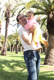 Father lifting little daughter at park. Young girl on father's arms at park with palm trees royalty free stock photo