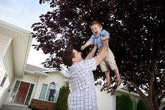 Father Lifting Son in Air stock image