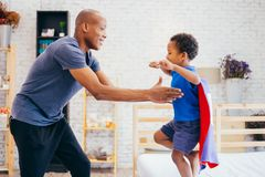 Father lifting son up with super hero costume at home.  Royalty Free Stock Image