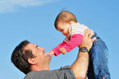 Father Lifts His Baby Girl Against Blue Sky Stock Image