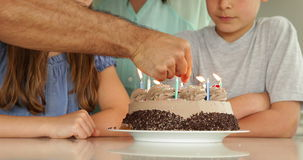 Father lighting candles on birthday cake for his family Stock Image