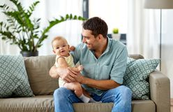 Father with little baby daughter at home. Family, fatherhood and people concept - father with little baby daughter at home royalty free stock images