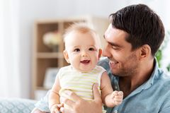 Father with little baby daughter at home. Family, fatherhood and people concept - father with little baby daughter at home royalty free stock photography