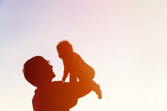 Father and little baby silhouettes play at sky Royalty Free Stock Photography
