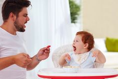 Father and little baby son having fun during dinner time. Cheerful father and little baby son having fun during dinner time Stock Images