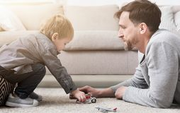Father and little boy playing with toys. Loving father and little boy playing together with toys in living room Stock Photos
