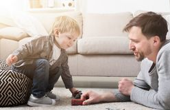 Father and little boy playing with toys. Father and little boy playing together with toys in living room Stock Images