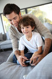 Father and little boy playing video game Stock Images
