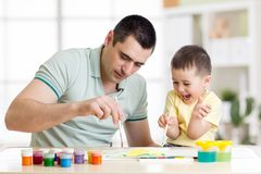 Father and little boy of three years having fun painting at home Royalty Free Stock Images