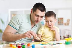 Father and little boy of three years having fun painting at home Stock Images