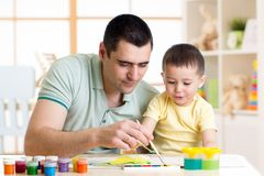 Father and little boy having fun painting at home Royalty Free Stock Image