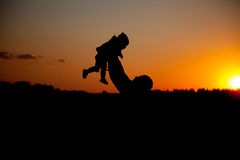 father and little child silhouettes play at sunset sky stock photos
