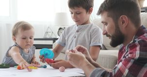 Father and little children playing with plasticine. Father with little children doing creative art and craft work at home stock footage