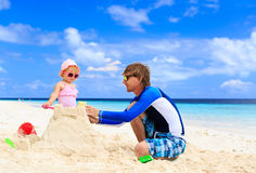 Father and little daughter building sandcastle on Stock Photos