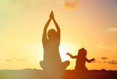 Father and little daughter doing yoga at sunset Stock Image