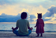 Father and little daughter doing yoga at sunset Royalty Free Stock Images