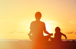 Father and little daughter doing yoga at sunset Stock Photos