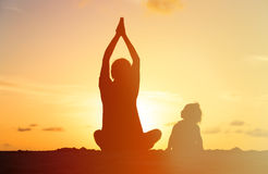 Father and little daughter doing yoga at sunset Royalty Free Stock Photography