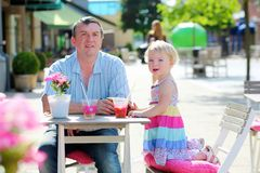 Father and little daughter drinking in cafe Stock Image