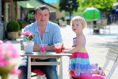 Father and little daughter drinking in cafe Stock Images
