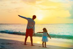 Father and little daughter fly play on sunset beach. Father and little daughter fly play on tropical sunset beach Stock Images