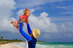 Father and little daughter having fun on the beach Stock Photo